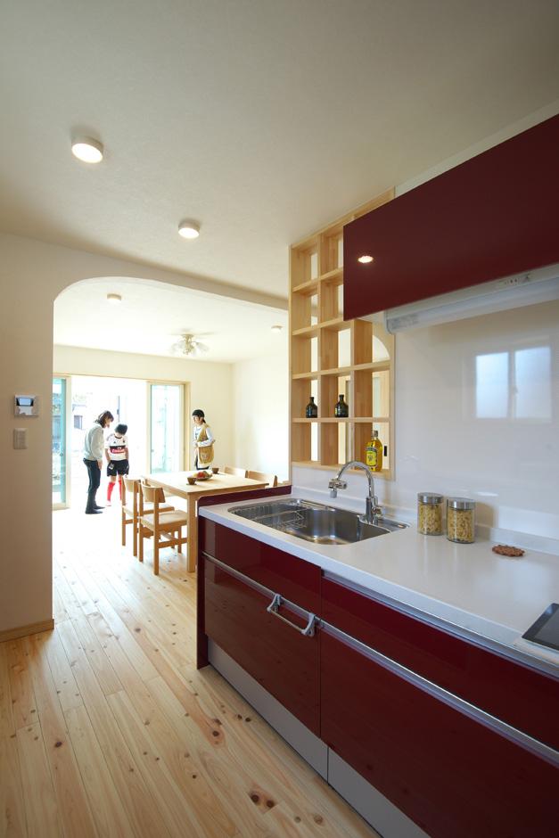 ワイズホーム|奥さまの希望で採用した赤いキッチンが、自然素材の空間によく映える。キッチン横の飾り棚はワイズホームが造作した
