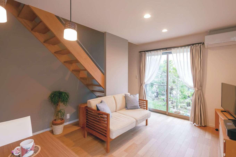 近藤建設工業【デザイン住宅、二世帯住宅、間取り】娘さんのLDK。そのまま残した中庭を囲むように建物が計画され、どの部屋にも緑と風が届く。床は上品なあたたかみを醸すチェリーを選択。壁は一面をグレーにし、落ち着きを添えた