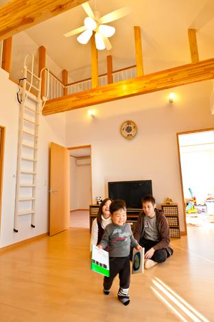 石上建設【子育て、収納力、二世帯住宅】大きな梁と高い天井が印象的な2Fリビング。勾配天井を利用したロフトもあり、室内を実際よりも広く、開放的に感じさせている。インテリアも白とブラウンに統一され、ペンションのようなおしゃれな空間に。家族が集まるリビングを中心に部屋が配置されているので、自然にみんなが顔を見合わせ、楽しい一家団らんが始まる。