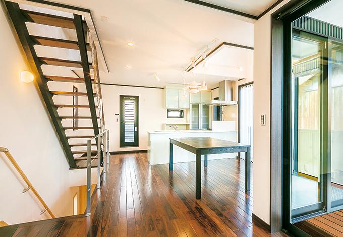 メタリックなスケルトン階段が、シャープな印象を与える。LDKに使用した落ち着いた色味の無垢ロックファーフローリングは、硬くキズがつきにくい