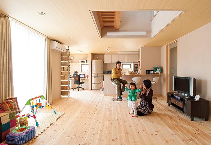 アキヤマ【子育て、自然素材、省エネ】重量木骨によるSE 工法がロングスパンの大空間を実現。保温性を高めるために天井高を下げる一方で、天井と建具の高さをそろえ、熱の滞溜の解消と視覚的な広がりを両立させている