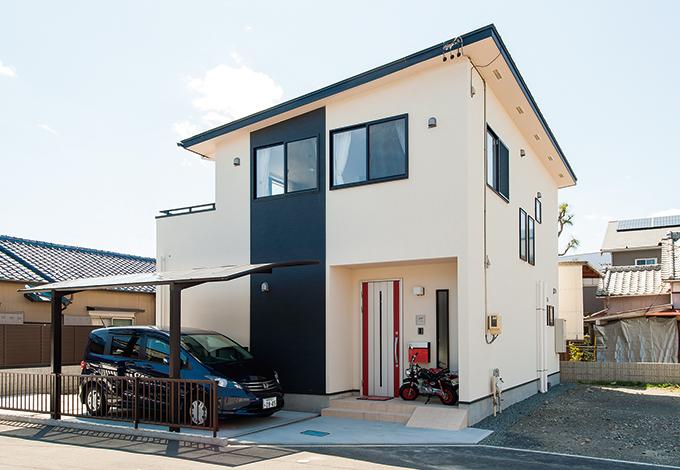 アキヤマ【子育て、自然素材、省エネ】パッシブデザインの効果を高める片流れのフォルム。軒の長さで日射量をコントロールしている。ホワイトの塗り壁、ブラックのサイディングに玄関の赤いドアがアクセント