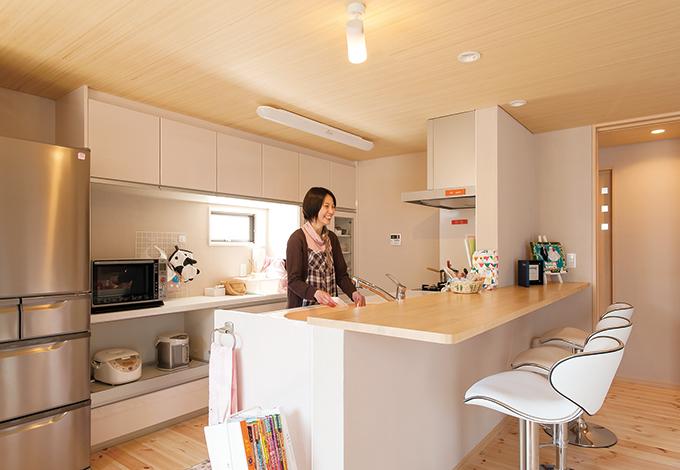 アキヤマ【子育て、自然素材、省エネ】準備や片付けの際も、来客との会話に参加できるようにと対面キッチンを希望。空間を広々と使いたいという思いから、ダイニングテーブルのない暮らしを選択した