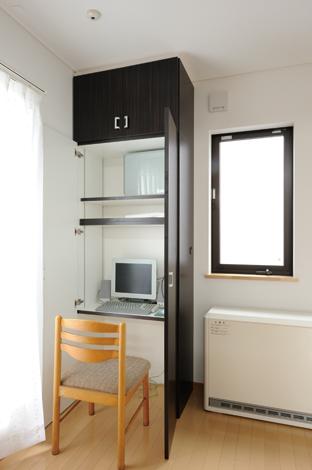 高棚の扉を開けばPCスペースに。部屋を広く見せ、無駄なスペースを作らないよう、天井までの高棚にこだわったご夫妻。スタイリッシュな扉を開くとPCスペースが登場