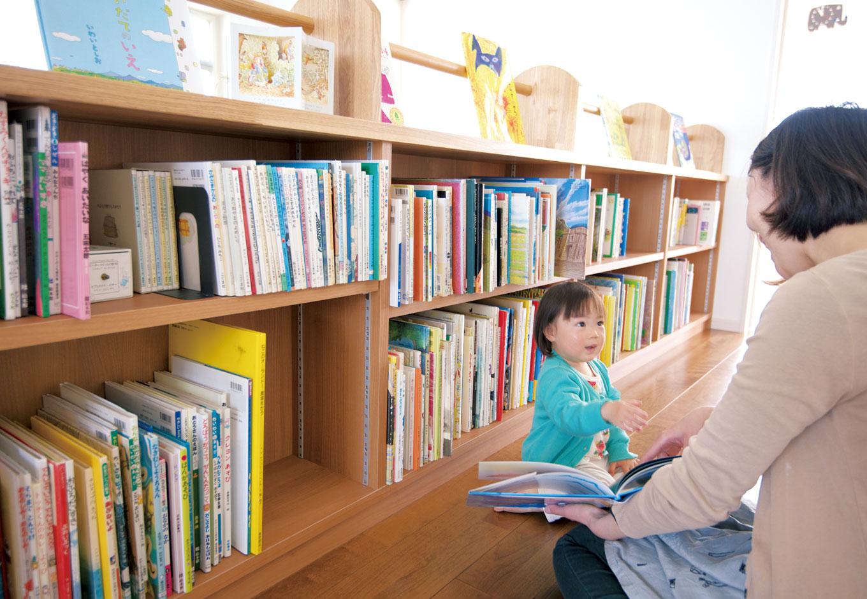 アキヤマ【デザイン住宅、子育て、省エネ】2階のホールに設けられた本棚には、絵本をたっぷり収納。明るく立ち寄りやすい雰囲気なので、子どもの好奇心をくすぐる。親子で素敵な読み聞かせの時間を過ごせる