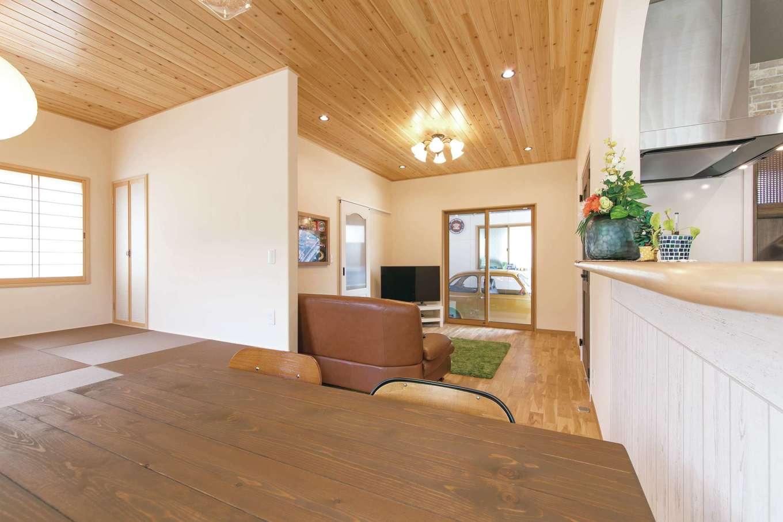 アキヤマ【自然素材、間取り、ガレージ】ダイニングからもガレージまで視線がのびる。小上がりの畳コーナーは、インテリアに合わせて茶色の畳をセレクト