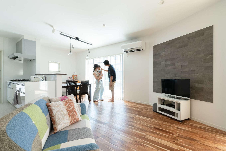 23畳のLDK。白い壁にアカシアの床とグレーのエコカラットが映える。家族がどこにいても様子が見える位置に対面キッチンを配置した