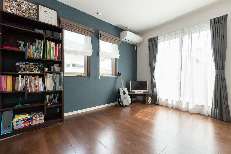 主寝室の一面にブルーのアクセントクロスを貼って、ご主人がギターを奏でる趣味部屋としても使っている。窓を開けると、変形に長くつながったベランダと直結