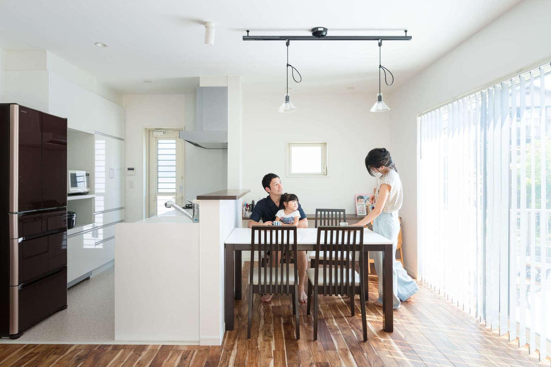 大きな窓からたっぷりの光が降り注ぐダイニングキッチン。ダイニングテーブルの後ろにカウンターを造作し、子どものスタディコーナーに。キッチンの床は掃除しやすいよう、クッションフロアを採用。リビングから手元が見えないようにカウンターを高くしたのもこだわり