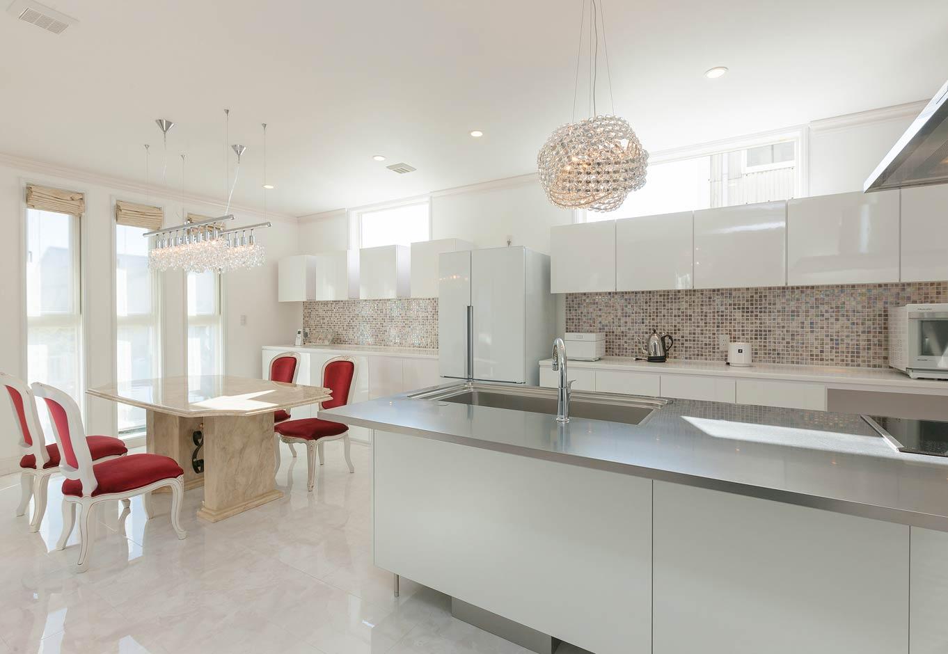 i.u.建築企画【デザイン住宅、建築家、インテリア】20帖の広々としたダイニングキッチン。造作の収納棚をデザインし壁には輸入モザイクタイル、照明はシャンデリアとした