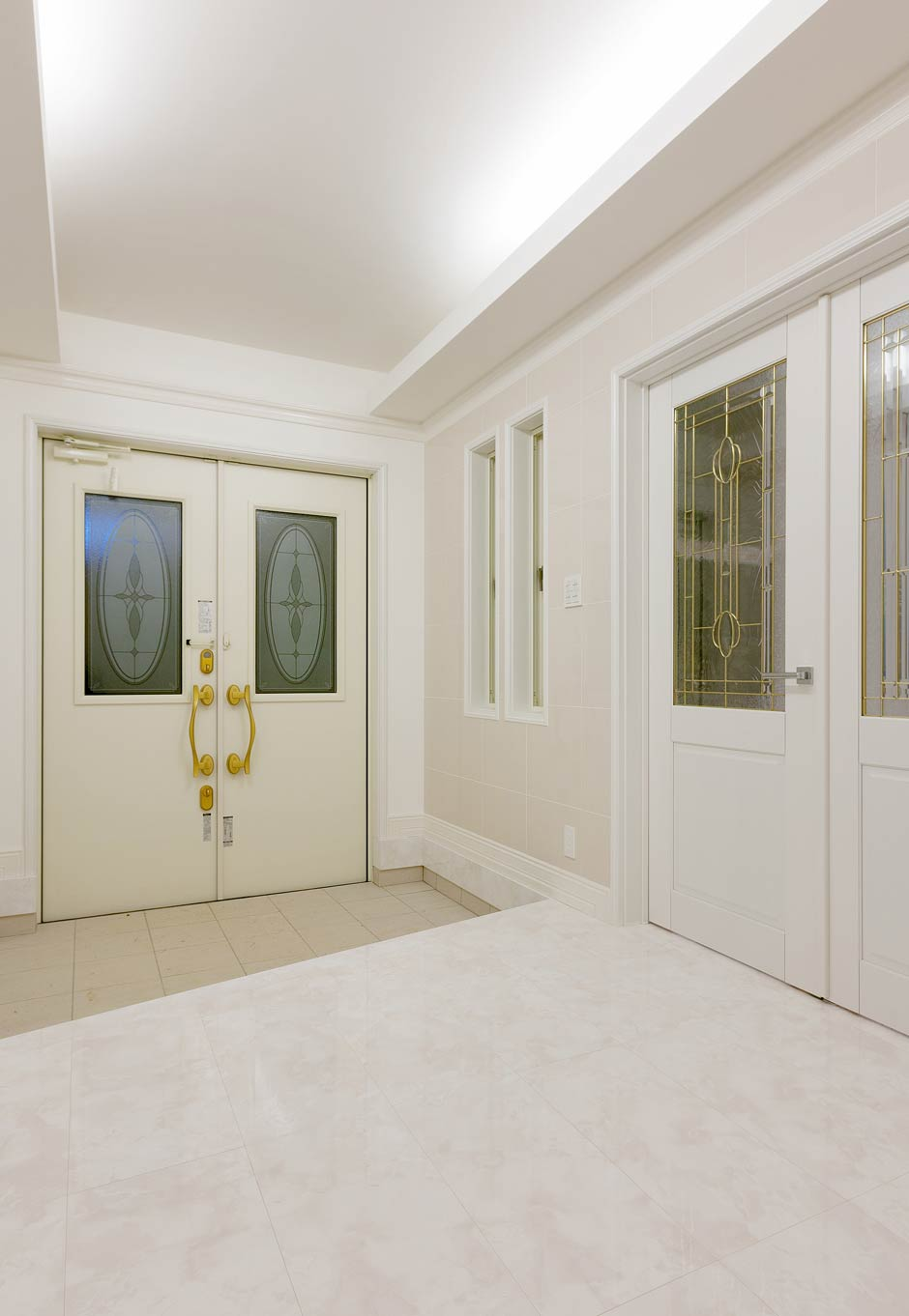 i.u.建築企画【デザイン住宅、建築家、インテリア】エントランス天井は間接照明に。壁は大理石調のタイルを使用。扉はステンドガラスの大きな親子扉に