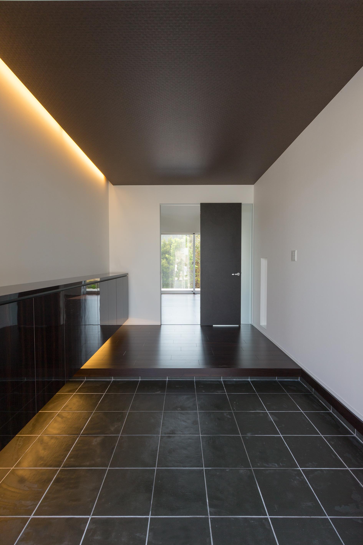 i.u.建築企画【デザイン住宅、建築家、インテリア】奥行のある直線的デザインのエントランス。造作の玄関収納の下と天井に間接照明を仕込み、天井をスッキリとさせている