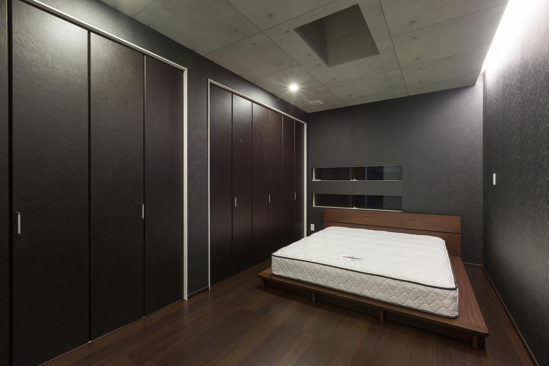 i.u.建築企画【デザイン住宅、建築家、インテリア】黒とコンクリート色でデザインした無機質なベットルーム。照明は壁面を照らす間接照明とした