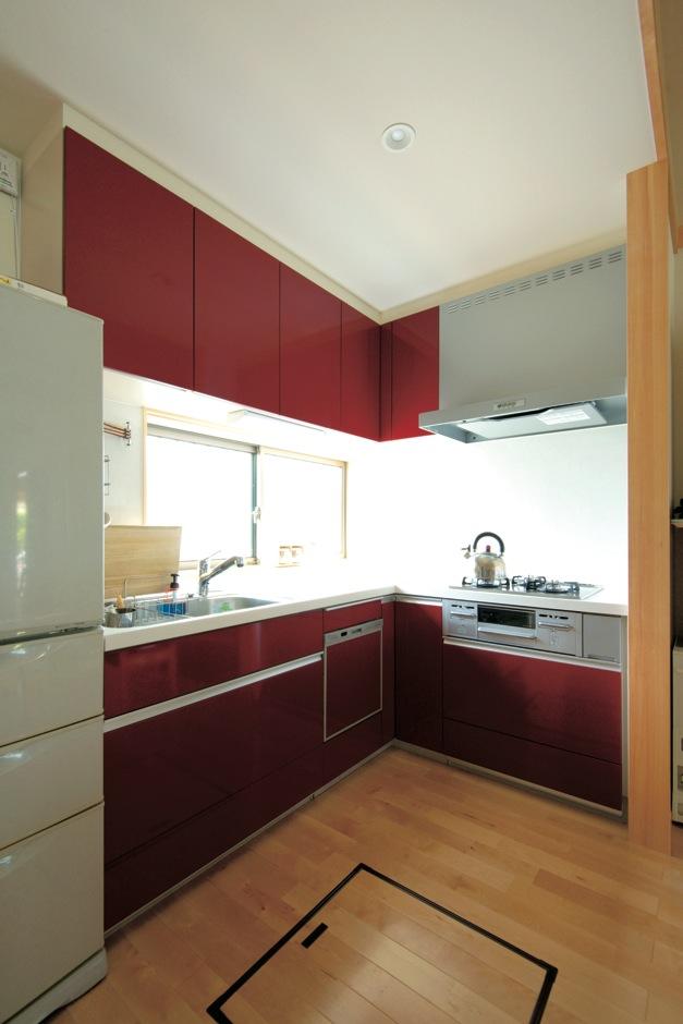 二世帯共有のキッチンはL字型。シンプルな部屋に鮮やかなワインレッドが映える