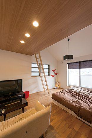大きな収納用のロフトが付いた寝室。広めに作ったので、ソファとテレビを置いたミニリビングも実現