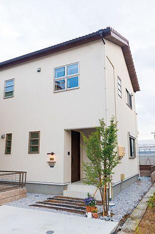2階の部屋の四窓がアクセントに。玄関までのアプローチに敷かれた枕木もお洒落