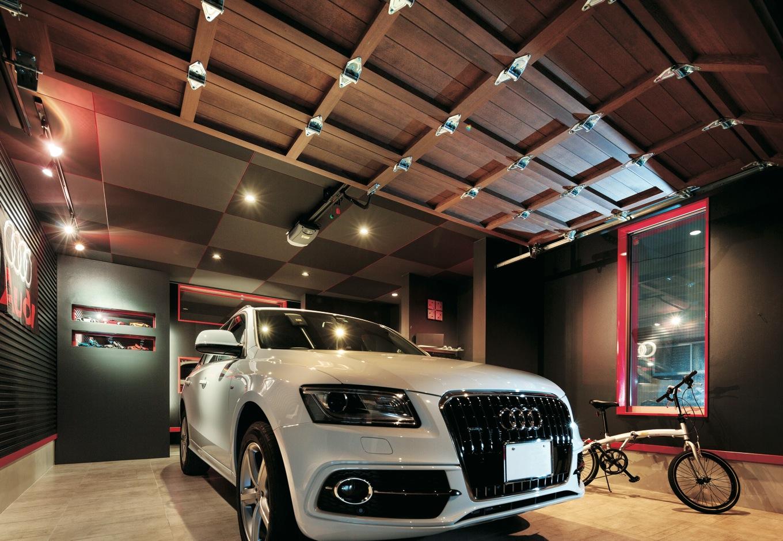 Dサポート【自然素材、間取り、ガレージ】主役となる車に当たる照明の位置まで考慮した、ご主人念願のガレージ。壁に掲げた車名のロゴフラッグは、柴田社長からのサプライズプレゼント