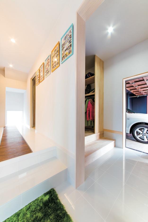 Dサポート【自然素材、間取り、ガレージ】大理石をベースに、家の中へと誘うように廊下の中央部分には木材を配した。ガレージとの間には大きなシューズクローゼットを設けている