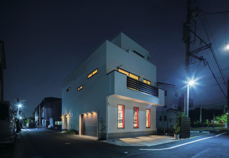 Dサポート【自然素材、間取り、ガレージ】昼はまぶしい白さを見せる塗り壁の外観は、夜は窓からこぼれる灯りやガレージ、エントランスの照明でぬくもりある表情に