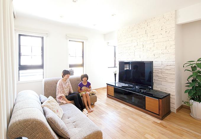 家族が集まるリビングは、チークのフローリングとレンガや塗り壁によりオシャレな空間に