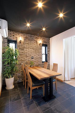 ご主人のかねてからの希望であった「レストランでディナーをしているような」を形にしたアンティークレンガとタイルを組み合わせたダイニング。窓や、壁の照明にもこだわり、レストランの個室を思わせる空間に仕上げた。ダイニングテーブルはDサポートで製作。空間に合わせて1つ1つ造作している