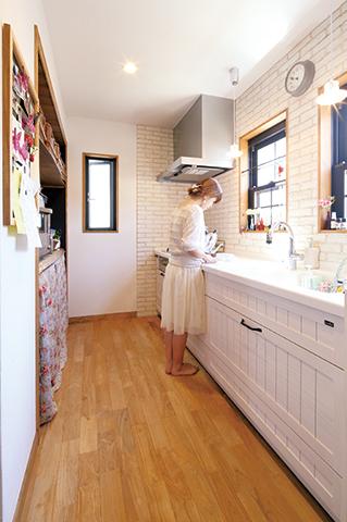 素焼きのレンガと真っ白な木製キッチンは、奥さまの「こんな感じにしたい」という希望を実現。 背面の収納棚は一枚板で造作。バスケットやカフェカーテンを活用して、食器や食材のストック を上手に収納