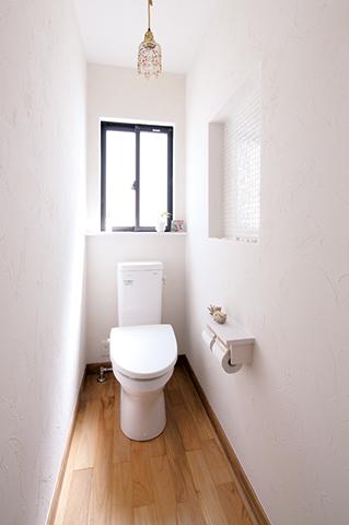シンプルながら、モザイクタイルを貼っ たニッチやキュートなシャンデリアがお洒落なトイレ