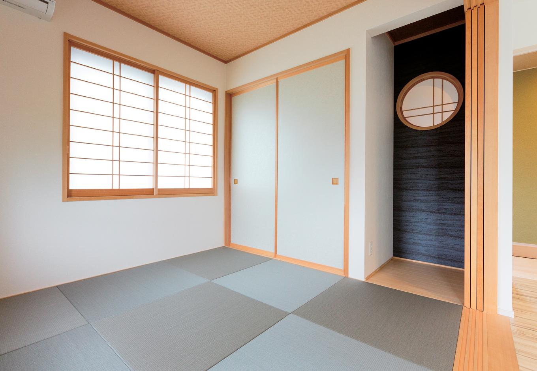 五朋建設【デザイン住宅、和風、間取り】リビングとひと続きになる和室。琉球畳と障子の桟のデザインで、モダンな印象に。玄関に面した壁には障子を貼った丸窓が