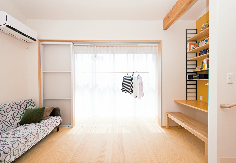 五朋建設【子育て、趣味、省エネ】2階リビングに設けた南面の大きな窓からはたっぷりの陽射しが注ぎ、洗濯物もよく乾く。 天井に格納できる可動式の物干しや、壁の裏にあるリビングからは見えない収納棚など、生活感を隠しながらも実用的な工夫がいっぱい。「新居で生活を始めてからは、花粉症の症状もずいぶんラクになりました!」と奥さま