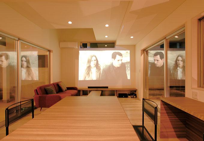 五朋建設【デザイン住宅、二世帯住宅、屋上バルコニー】夜のリビングはホームシアターに早替わり。広い壁に直接映像が映し出 され、家族揃って楽しんでいる