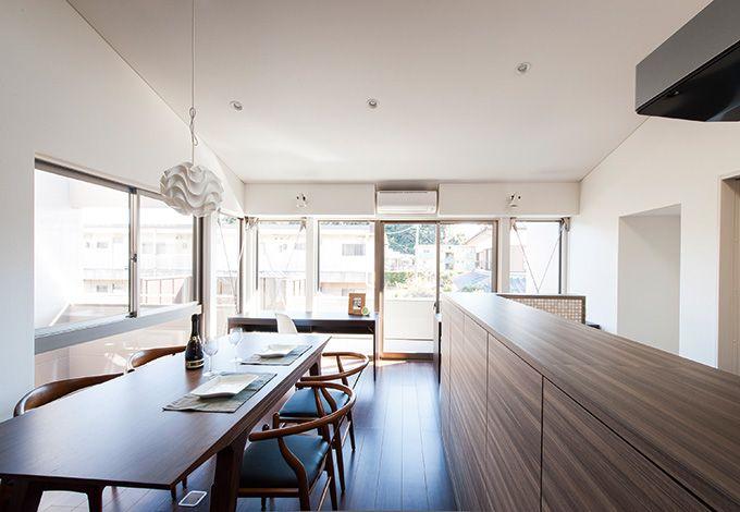 五朋建設【デザイン住宅、間取り、建築家】ダイニングキッチンは、窓を広く設けて開 放感を演出した。左手からはライトコート を望むことができる。キッチンカウンター の下も大容量の収納スペース