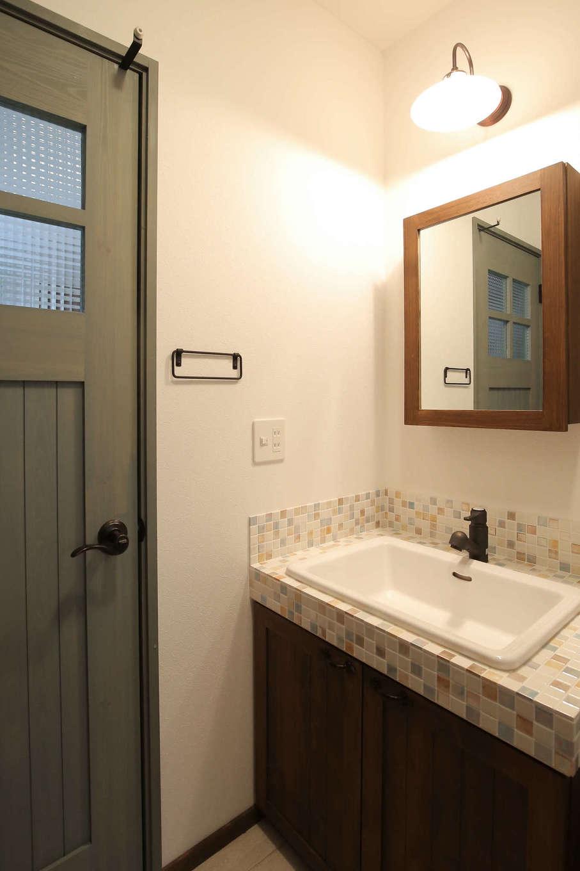 サンエフホーム【デザイン住宅、輸入住宅、自然素材】モザイクタイルを使った洗面台。かわいらしい雰囲気に合わせた鏡も造作で裏が収納になっている
