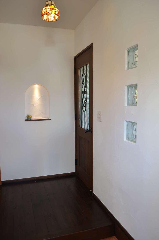 サンエフホーム【デザイン住宅、輸入住宅、自然素材】漆喰のやさしい質感を感じる玄関。扉のアイアンは図面から書き起こしたオリジナル