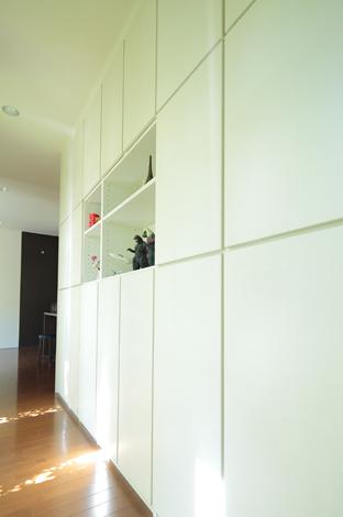 久保田建設【デザイン住宅、趣味、間取り】渡り廊下一面は収納と飾り棚。ここに物をまとめることで、リビングはすっきりと