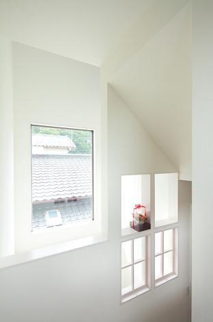 久保田建設【1000万円台、収納力、狭小住宅】建物越しに母屋の天窓へ光が届くよう、吹き抜けに大きなFIX窓を設けた