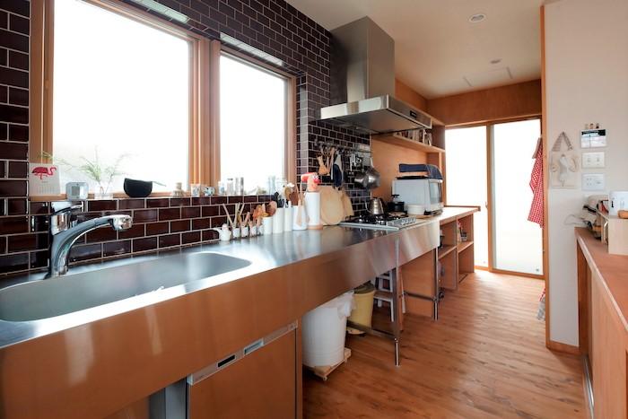 瀧建設 一級建築士事務所【子育て、収納力、自然素材】シンプルなキッチンの奥にはパントリーを。どこに何をしまうかあらかじめ収納計画を立て、それに合わせて造作。手が届きやすい上部棚は料理本を収納