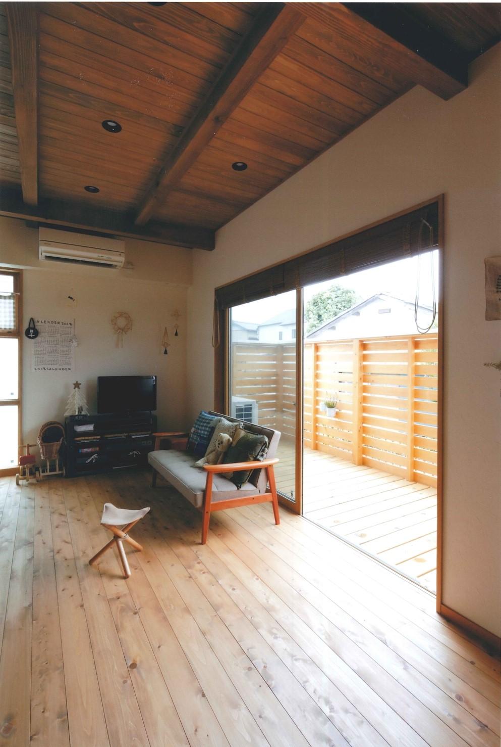 瀧建設 一級建築士事務所【子育て、収納力、自然素材】リビングの天井は無垢材の現しに。リビングの延長線上にウッドデッキがあり、空間に広がりを生んでいる