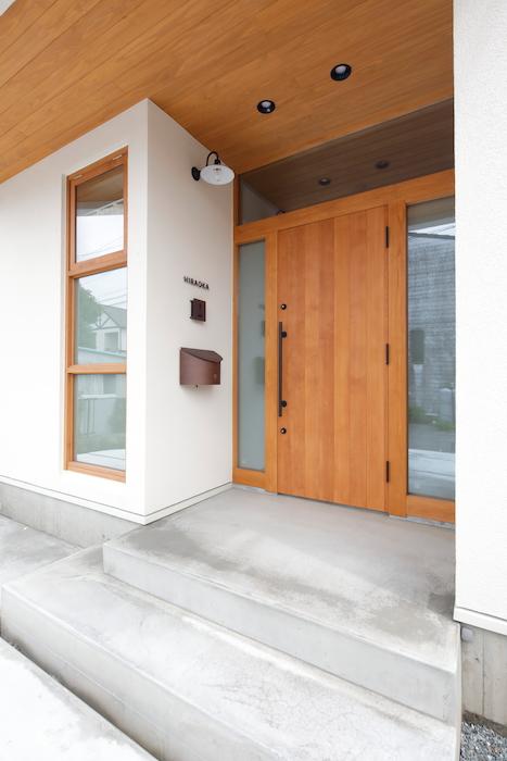 瀧建設 一級建築士事務所【子育て、収納力、自然素材】ドアや軒天・窓枠の木質と、モルタルの質感がマッチした玄関ポーチ。ライトは雑貨好きの奥さまがチョイス