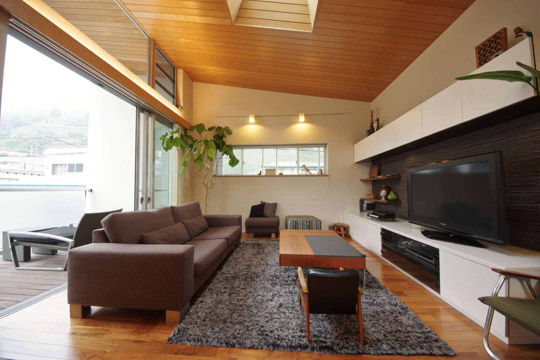 イセキ建設【静岡市葵区唐瀬3丁目4-4・モデルハウス】外に向かうほど高くなる勾配天井と、大窓・ハイサイドライト(高窓)・天窓の相乗効果で、他にない明るく開放感のあるリビングに。外部バルコニーまで連続する天井板貼は、より広がりを強調する意匠的な役割も大きい