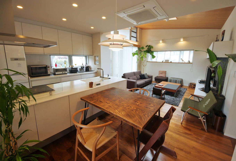 イセキ建設【静岡市葵区唐瀬3丁目4-4・モデルハウス】リビングとは天井高を変えたダイニング・キッチン。ひとつづきのLDKに変化をつけた。北欧家具の名作Yチェアやルイス・ポールセンのライトがぴったりマッチ