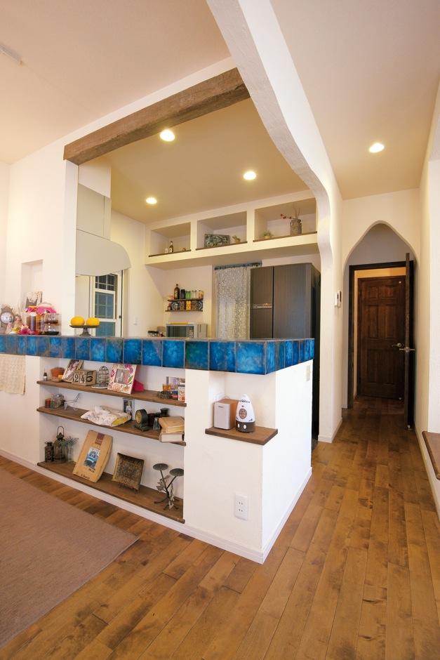 ハートホーム【デザイン住宅、輸入住宅、インテリア】奥さまがひと目ぼれしたタイルのブルーが引き立つようにコーディネート。カウンターと冷蔵庫上部には棚を造作し、見せながら収納している。一方、見せたくない家電や食品ストックは、ひと続きの家事室に。食器棚を造作せずに済み、コストを抑えられた。今ではここで料理教室を開催。家が完成してから、思い描いていた暮らしを手に入れる事が出来たと奥様も大満足