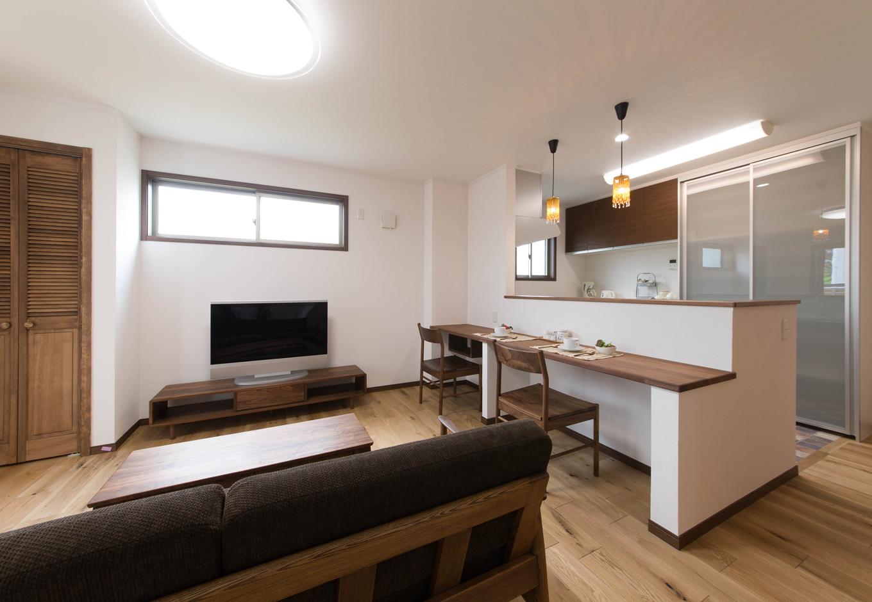 ハートホーム【デザイン住宅、二世帯住宅、自然素材】ご両親のLDK。あえて部屋の広さを削って設けた左手のデッキから、たっぷりの光と風  がもたらされ、長年の不満が解消された。床には味わい豊かなアンティークオークを選択