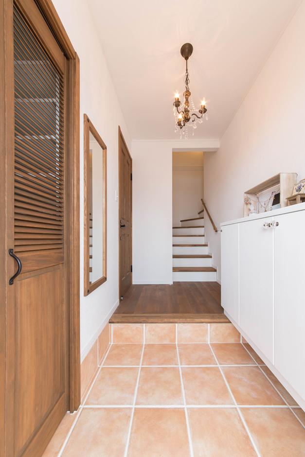 ハートホーム【デザイン住宅、二世帯住宅、自然素材】シューズクロークを備えた子世帯の玄関。奥の扉で親世帯と気軽に行き来できるようになっている。階段は踏面を広くするよう要望 。荷物の上げ下げもしやすくて正解だった