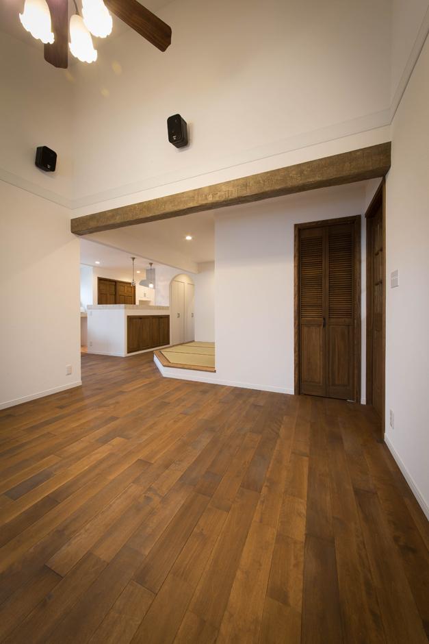 ハートホーム【デザイン住宅、二世帯住宅、自然素材】勾配天井が開放感を演出する2階のリビング。アンティーク風に仕上げた梁や垂れ壁、段差などにより、穏やかにゾーン分けがなされる。収納も随所に用意され、空間のスッキリに貢献