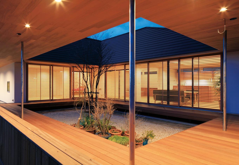 ハートホーム【デザイン住宅、自然素材、平屋】内側の屋根は急勾配でシャープな印象に。回廊は照明付きで夜もお酒やバーベキューを楽しめる。中庭に面した窓には木のルーバーを造作。窓を開け放すと気持ちのいい風が入ってくる