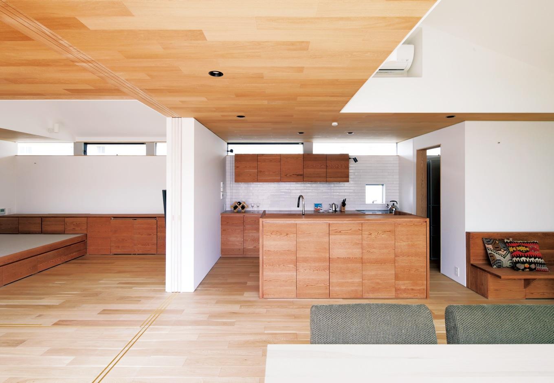 ハートホーム【デザイン住宅、自然素材、平屋】キッチンはオリジナルのアイランド型。隣接するご主人の居室との間の壁に建具が収納され、閉めれば個室になる