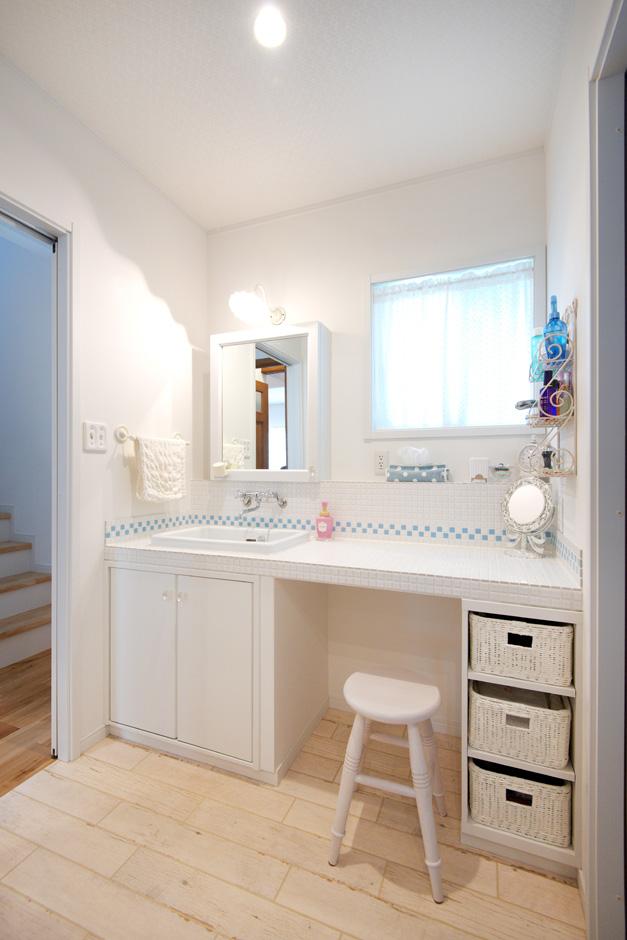 ハートホーム【自然素材、ガレージ、インテリア】白タイルに奥さまの好きなブルーのタイルをワンポイントで使った造作洗面台。洗面ボウル下の収納は「ぬれてもよい素材を選択して正解でした」と奥さま。洗面所と浴室の間に脱衣所を別に設け、誰かがお風呂を使っている時も洗面所を使用できるようにした