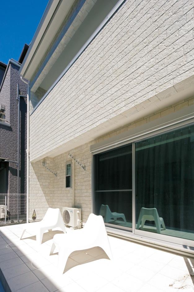 ハートホーム【デザイン住宅、間取り、インテリア】白いテラスはリビングの延長として部屋を広く見せる効果大。外でホットプレートが使えるようにコンセントを設置してある