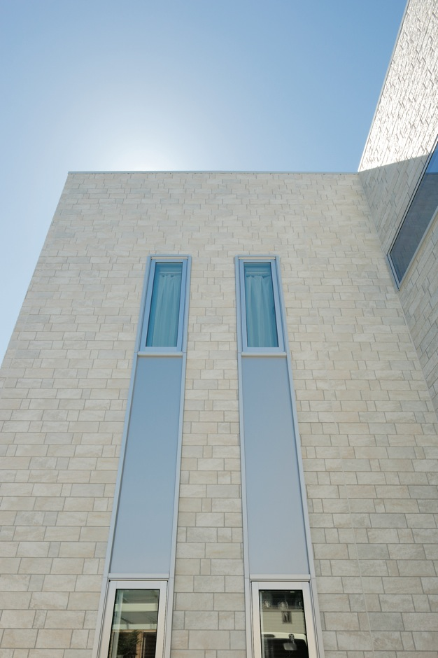 ハートホーム【デザイン住宅、間取り、インテリア】外壁は重厚感のあるベージュの石張り調。白い塗り壁よりも汚れが目立たないメリットも