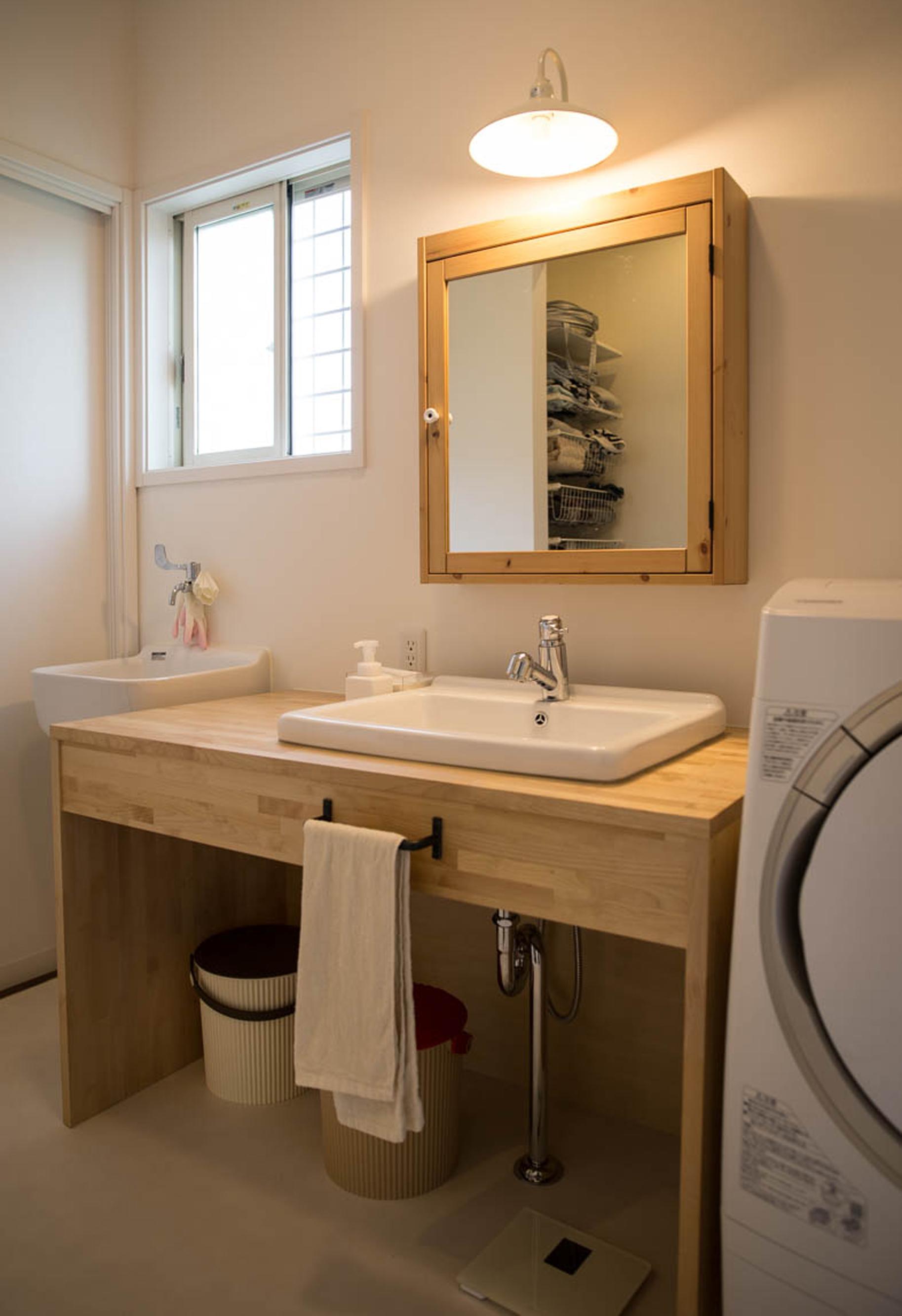 ハートホーム【デザイン住宅、収納力、間取り】洗面所だけはあえてテイストを変えてナチュラルで明るいイメージに。鏡の内側に収納があり、木の造作洗面台の上に物を置かずにすむ。奥のスロップシンクはおむつ洗いや趣味のソーイングで使う生地の水通し用に